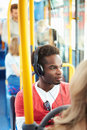 Man wearing headphones listening to music on bus journey his own with passengers in background Royalty Free Stock Photos