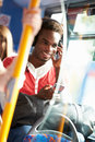 Man wearing headphones listening to music on bus journey holding mobile phone smiling Stock Images