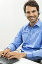 Man wearing headset giving online chat and support attractive unshaven young a offering on a client services of help desk as he Royalty Free Stock Image