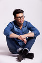 Man wearing jeans shirt and glasses, sitting Royalty Free Stock Photo