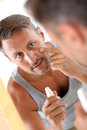 Man wearing an undershirt cleaning his skin in bathroom applying cosmetics on face Royalty Free Stock Image