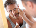 Man wearing undershirt taking care of skin in bathroom applying cosmetics on his face Royalty Free Stock Photo
