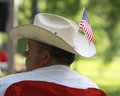 Man wears cowboy hat with american flag at tea party rally wearing a an on it a a park flags Stock Images