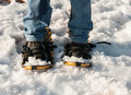 Man wears snowshoes and blue jeans in the winter Stock Images