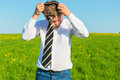 Man wears a tie in the morning green field Royalty Free Stock Image