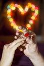 The man wears a woman s finger ring against backdrop of colorful heart shaped bokeh Stock Images