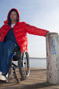 Man in wheelchair on boardwalk handicapped at a lake Royalty Free Stock Photos