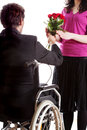 Man on wheelchair giving a flowers to his girlfriend Royalty Free Stock Images