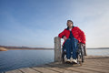 Man in a wheelchair handicapped watching the sea Stock Photo