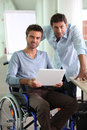 Man in wheelchair holding laptop Royalty Free Stock Images