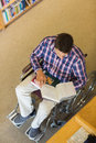 Man in wheelchair reading a book in library high angle view of the Royalty Free Stock Photos