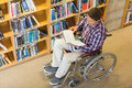 Man in wheelchair reading a book in the library high angle view of Stock Images