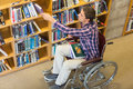 Man in wheelchair selecting book in the library high angle view of a from bookshelf Royalty Free Stock Image