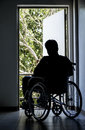 Man on a wheelchair silhouette of depressed disabled sitting looking out an open door Royalty Free Stock Image