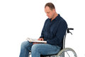 Man in wheelchair young is reading a book Royalty Free Stock Photography