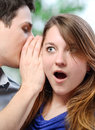 Man whispering in the ear of his surprised wife portrait men Stock Photography