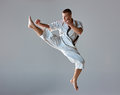 Man in white kimono training karate and black belt over gray background Royalty Free Stock Photo