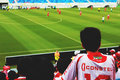 Man on White and Red Jersey Shirt Looking at Sport Game