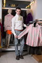 A man in a white shirt with jabot chooses clothes clothing store Stock Photography