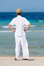 Man in white suit on a tropical beach back view with his hands his hips and hat standing Royalty Free Stock Photo
