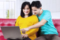 Man with wife pregnant using laptop portrait of asian men on couch Stock Image