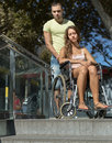 Man and wife in wheelchair on stairs Royalty Free Stock Photo