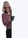 Man in winter clothes and fur hat is pointing to a blank board young on white background Royalty Free Stock Images