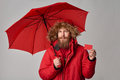 Man in winter jacket with umbrella showing blank credit card Royalty Free Stock Photo