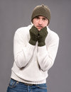 Man in winter mittens and hat handsome on a gray background Stock Images