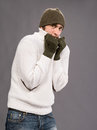 Man in winter mittens and hat handsome on a gray background Royalty Free Stock Images