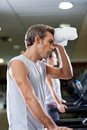 Man wiping sweat with towel at health club side view of young men Royalty Free Stock Photo