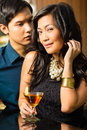 Man and woman in asia at bar with cocktails asian flirting intimately drinking Stock Photos