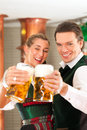 Man and woman with beer glass in brewery glasses bavarian tracht front of a brew kettle Royalty Free Stock Images