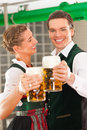 Man and woman with beer glass in brewery glasses bavarian tracht front of a brew kettle Stock Images