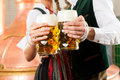 Man and woman with beer glass in brewery glasses bavarian tracht front of a brew kettle Royalty Free Stock Photos