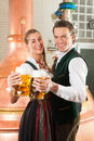 Man and woman with beer glass in brewery glasses bavarian tracht front of a brew kettle Stock Photography