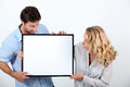 Man and woman with blank board women astounded by a left for your image Royalty Free Stock Image