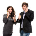 Man and woman with cell phones women showing ok sign Royalty Free Stock Images