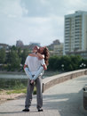 Man and woman in the city photo girls men on background of cityscape on waterfront summer Stock Photography