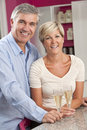 Man & Woman Couple Drinking Champagne In Kitchen Stock Photo