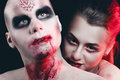 Man and woman in the dark women with blood body art Royalty Free Stock Image