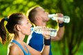 Man and woman drinking water from bottle after Royalty Free Stock Photo