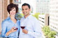 Man and woman drinking wine on outside balcony portrait of men women a city background with trees Royalty Free Stock Images