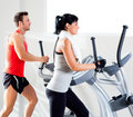 Man and woman with elliptical cross trainer at gym Royalty Free Stock Photos