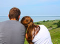 Man and woman embracing look look at the sky and water rear view Stock Photos