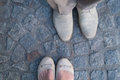 Man and woman face to face stand on cobbles. Focus on the footwear. Royalty Free Stock Photo