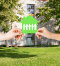 Man and woman hands with paper house real estate family home concept isolated closeup picture of male female holding green Royalty Free Stock Images