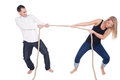 Man and woman having a tug of war women each leaning back straining with the effort pulling the rope in opposite directions full Stock Image