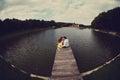 Man and woman hug sitting on the bridge at lake Royalty Free Stock Photo