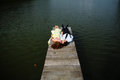 Man and woman lay on the bridge on the lake Royalty Free Stock Photo